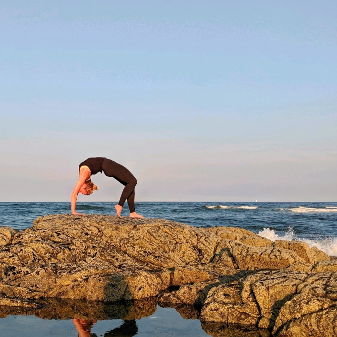 SomerJill in wheel pose on the rocks at the beach.